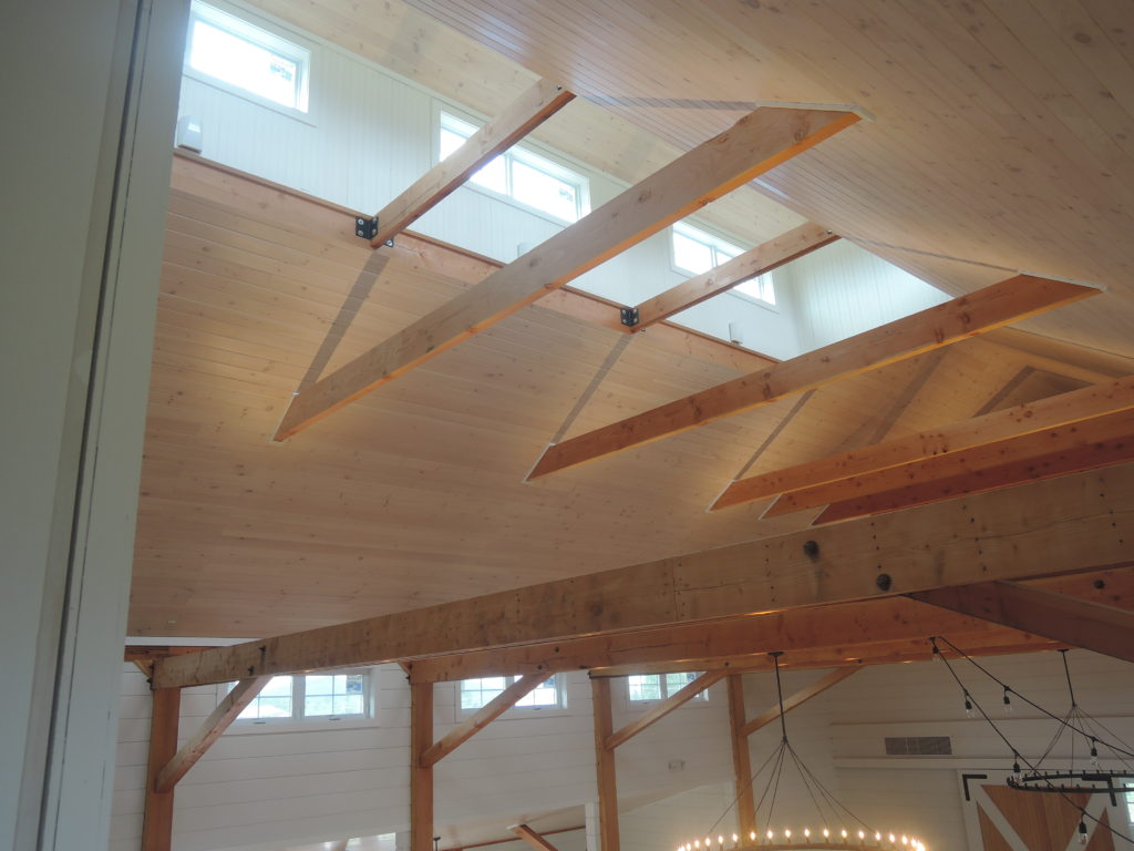 A picture of the ceiling of a Wedding Barn in Vermont showing the framing timbers, the wood ceiling, and sunlight streaming through the cupola