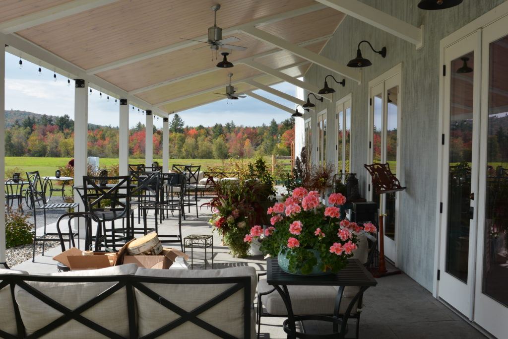 A picture of a veranda of a a Wedding Barn in Vermont with iron cocktail tables and chairs and decorated with floral bouquets