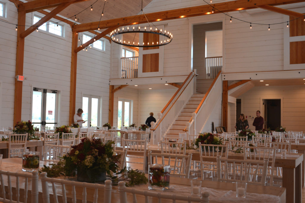 A picture of a banquet in a Wedding Barn in Vermont with people setting up decorations