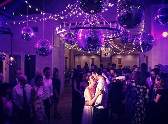 A picture of a wedding reception dance in a Wedding Barn in Vermont with Christmas lights and disco balls. A crowd watches the Bride and Groom first dance