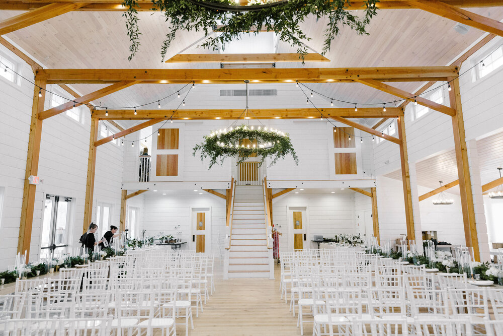 A picture of a Wedding Barn in Vermont with white chairs arranged for guests and two women setting up decorations